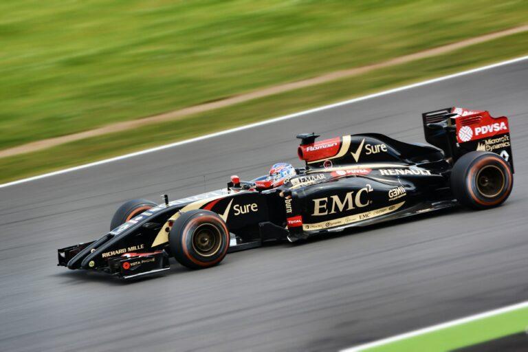 A black F1 race car speeding on a race track